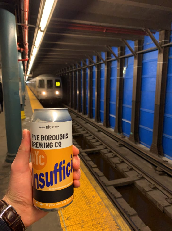 hand holding a beer in front of a subway train