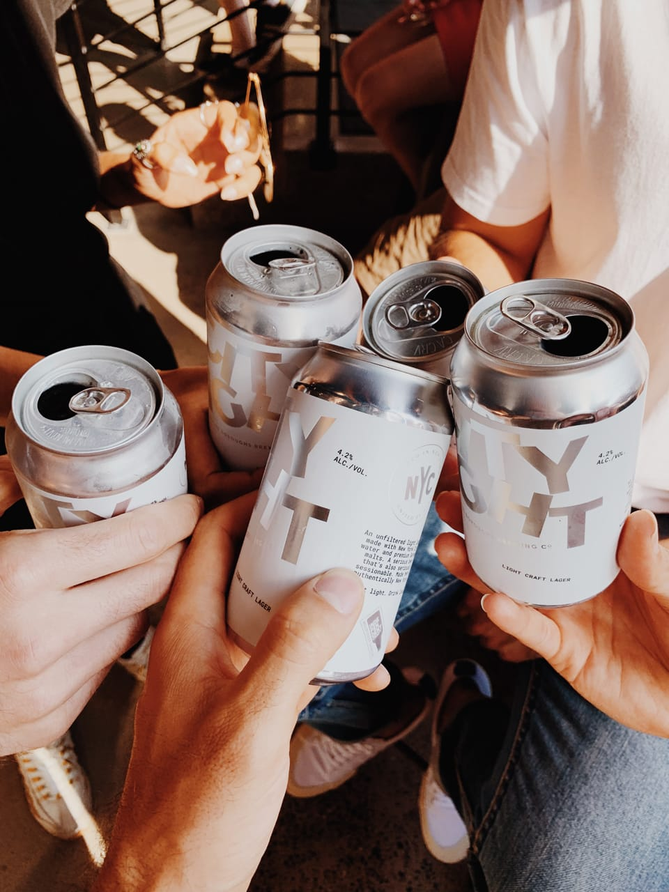people holding city light beer cans for a cheer